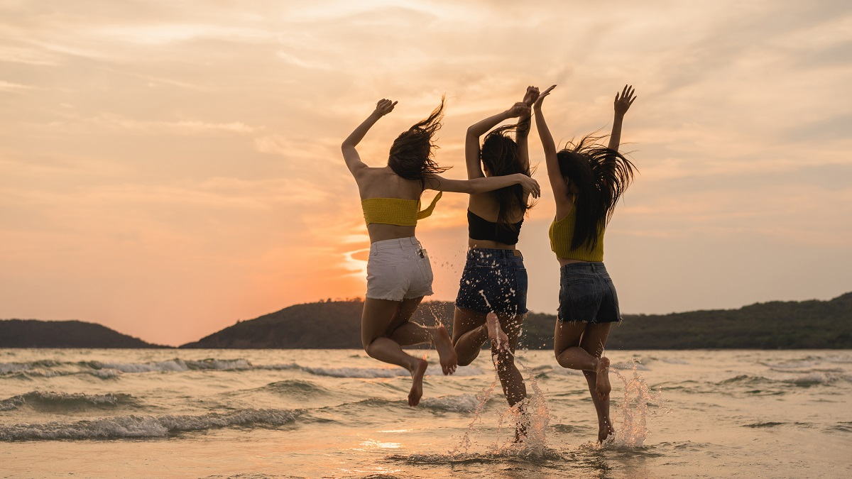 Group Of Three Asian Young Women Jumping On Beach, Friends Happy