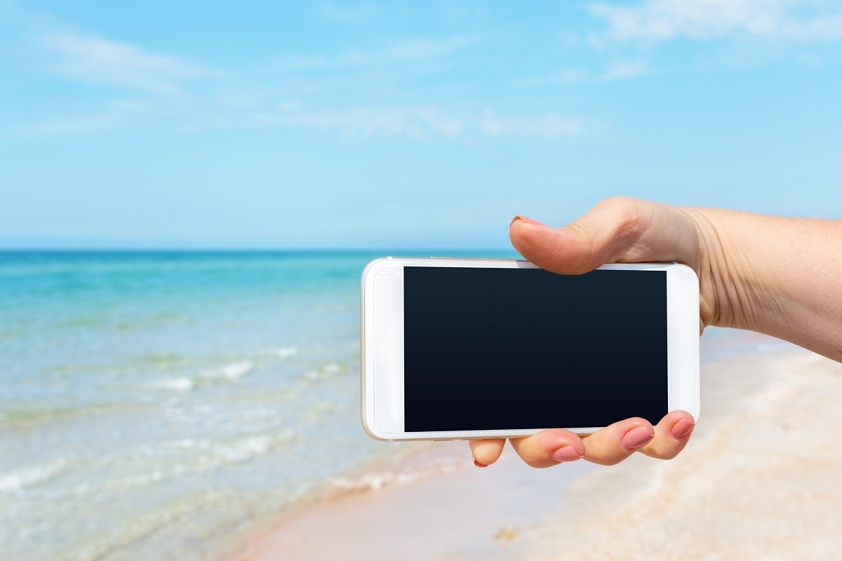 Beautiful Woman's Hand Using Smart Phone At Beach