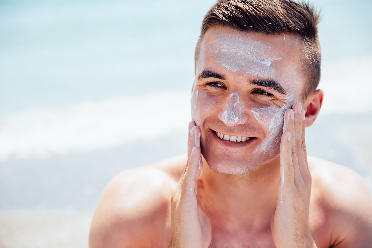 Cheerful Man Puts The Lotion On Face To Protect A Skin, On The Beach