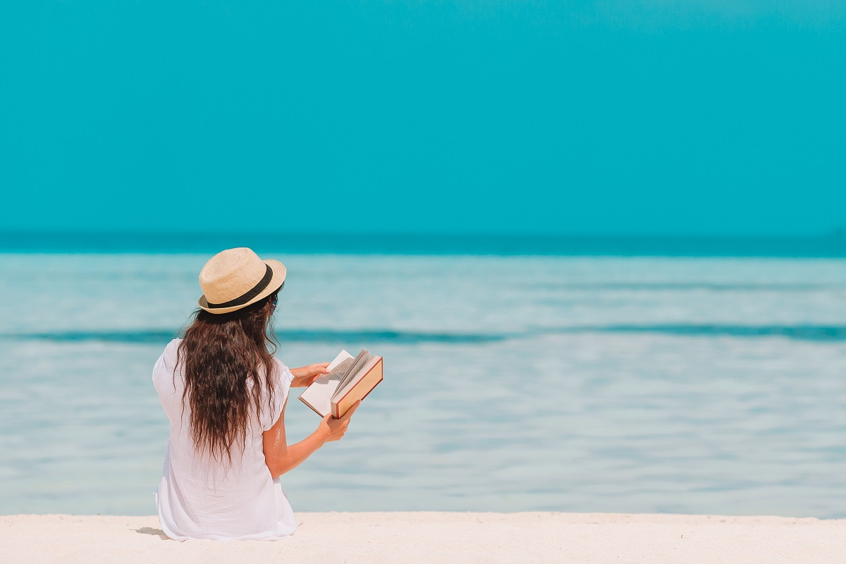 Portrait Of A Young Woman Relaxing On The Beach, Reading A Book