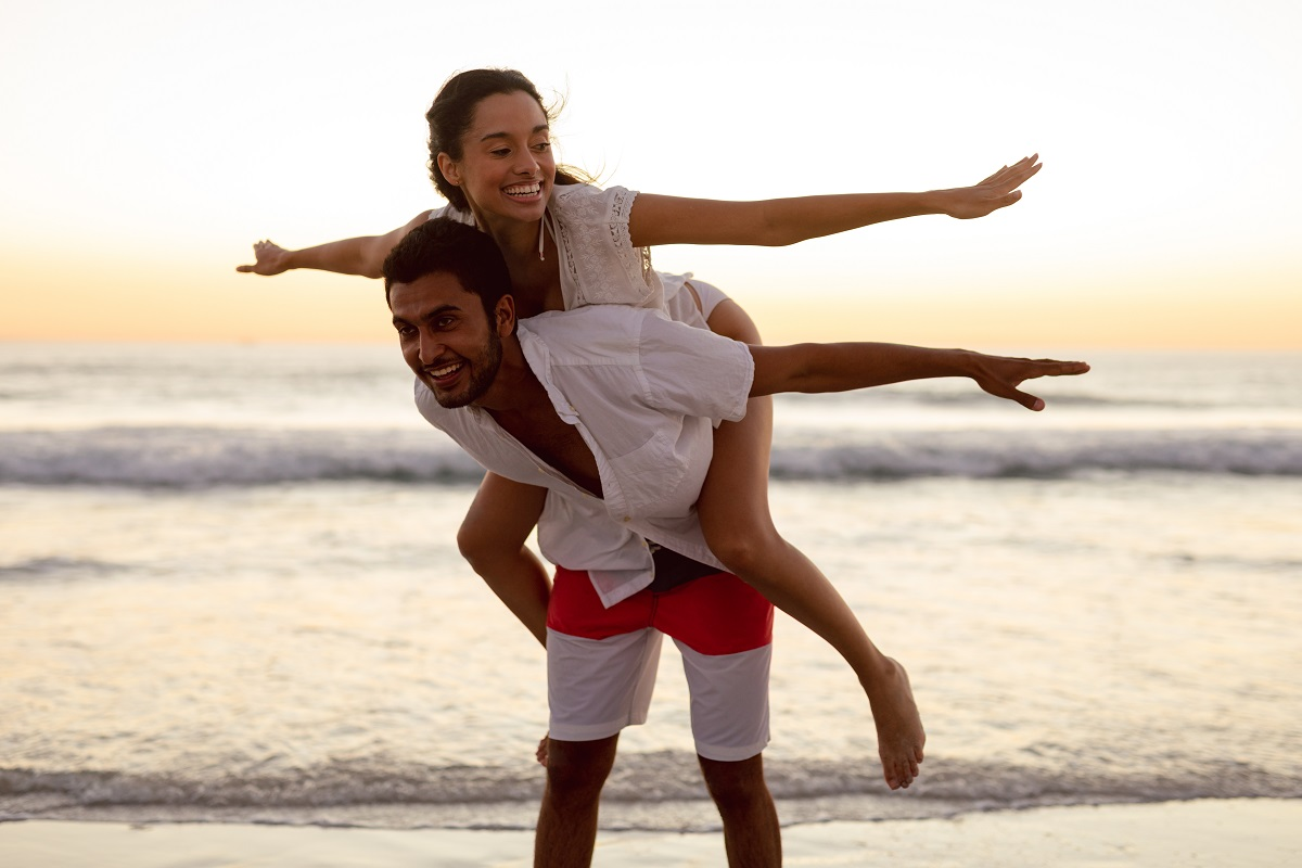 Young Man Giving Piggyback Ride To Woman On The Beach