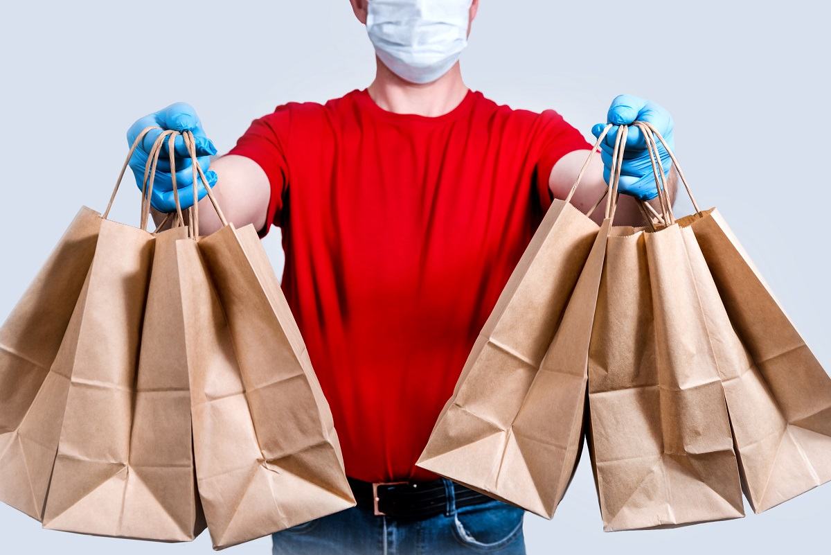 Safe Delivery. A Courier In A Red Uniform And Protective Mask And Gloves Holds A Large Order, Many Paper Bags, Contactless Delivery Food In Quarantine. Donation Of Volunteers. Zero Waste.