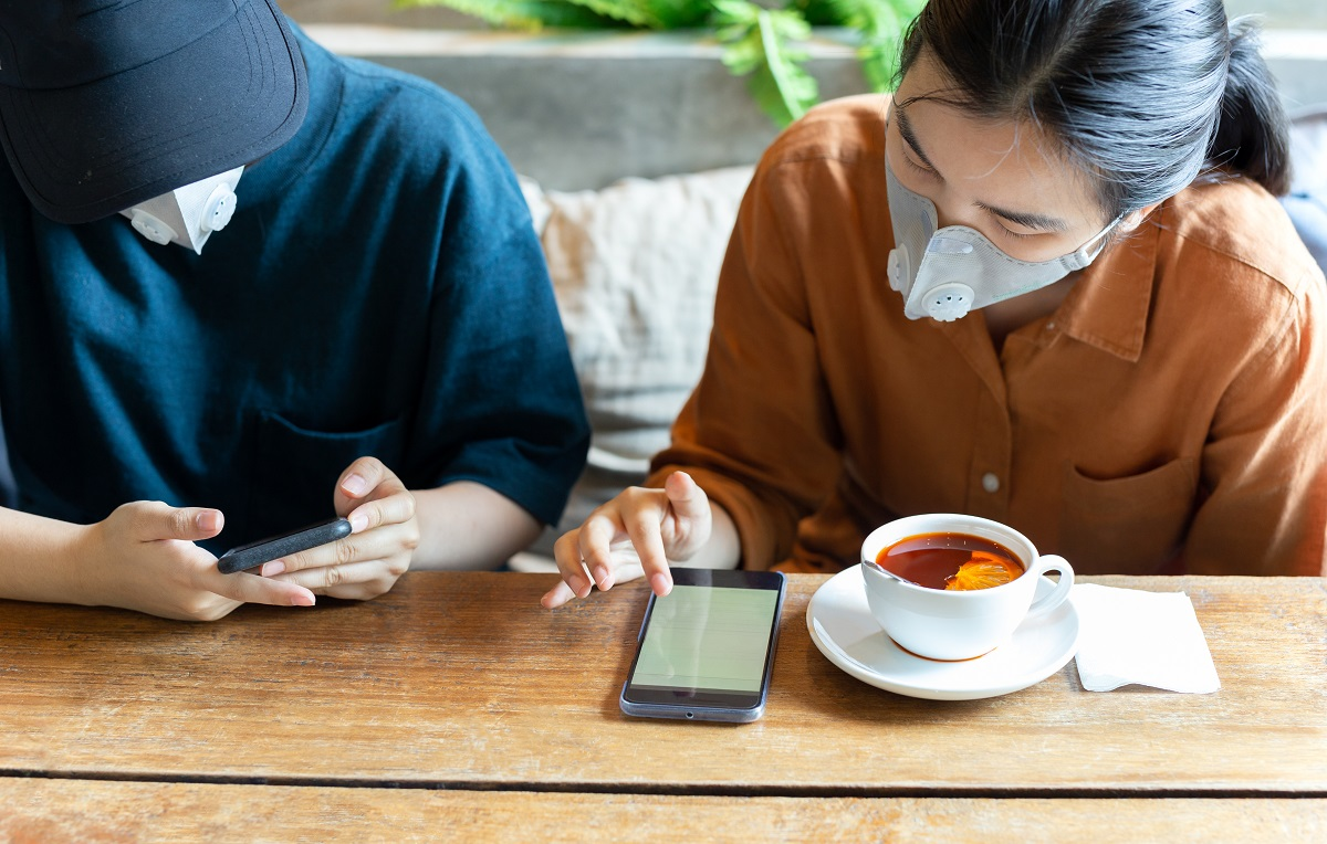 Two Womans In Protective Mask Prevent Covid 19 Using Cell Phone And Drinking Lemon Tea In Cafe.